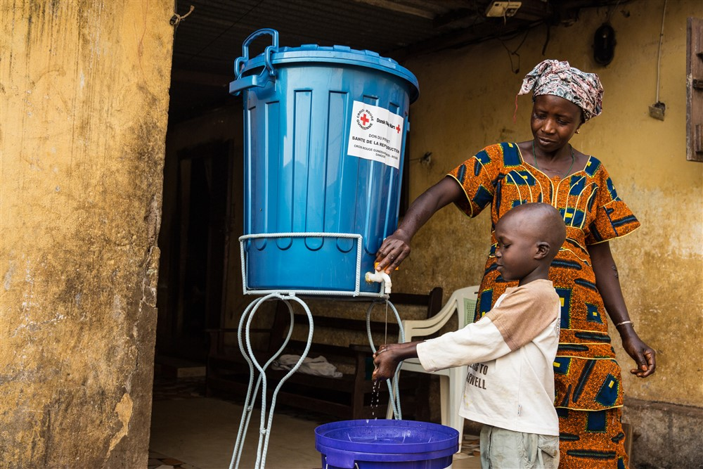Family provided with buckets and chlorine and taught how to wash hands properly at home during an Ebola outbreak. Photo UNMEER /Martine Perret