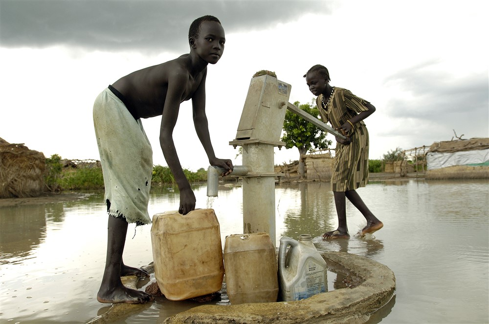 Children displaced by flooding in South Sudan collect water from a submerged hand pump. Photo UNMIS
