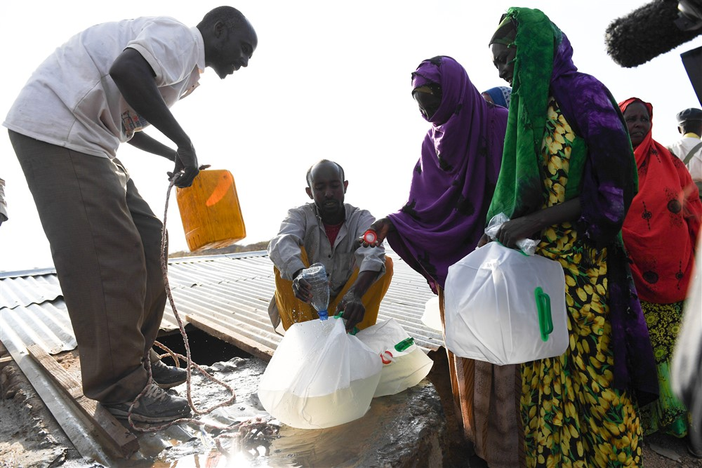 Women who were internally displaced by the ongoing drought in Somaliland receive water at a UNICEF-supported water distribution point in Laaca village near Gabiley, Somaliland. UN Photo/ Omar Abdisalan