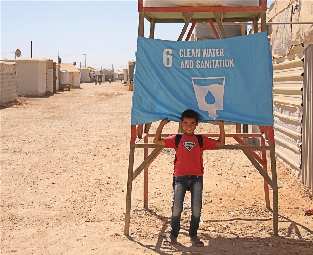 A child from the Za'atari Refugee Camp in Jordan raised a flag to represent Goal 6, Safe Water and Sanitation. Photo: UNICEF Jordan/badran