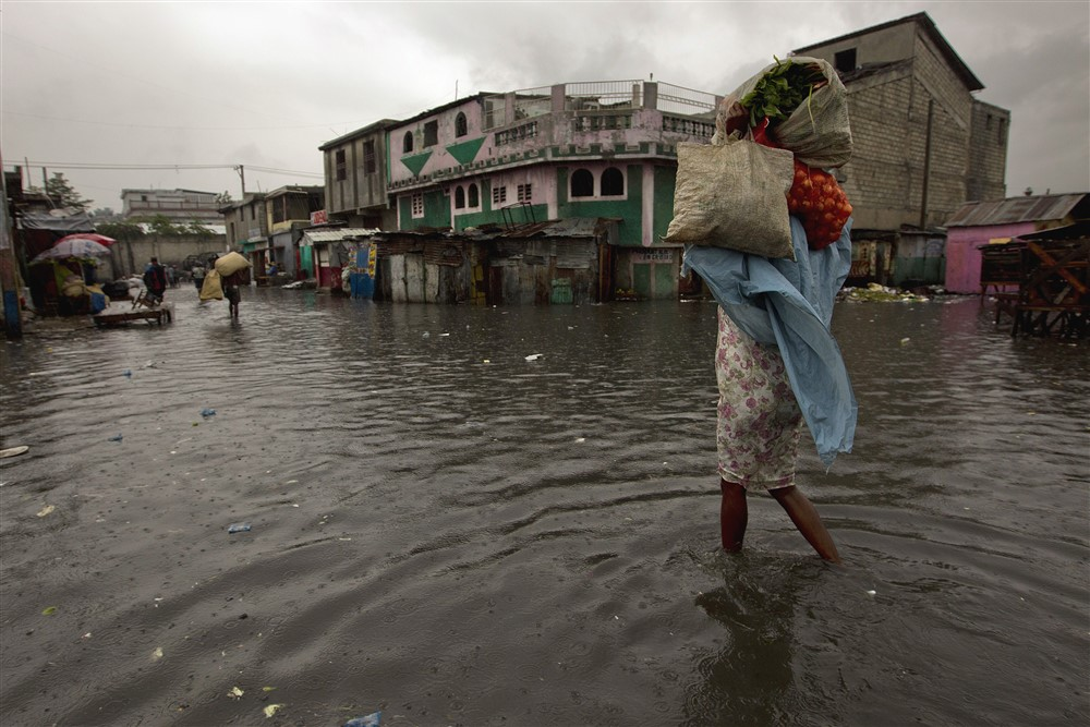 A woman walks through a flooded market in Port au Prince. Hurricane Sandy passed to the west of Haiti October 25, 2012 causing heavy rains and winds, flooding homes and overflowing rivers. Photo Logan Abassi UN/MINUSTAH