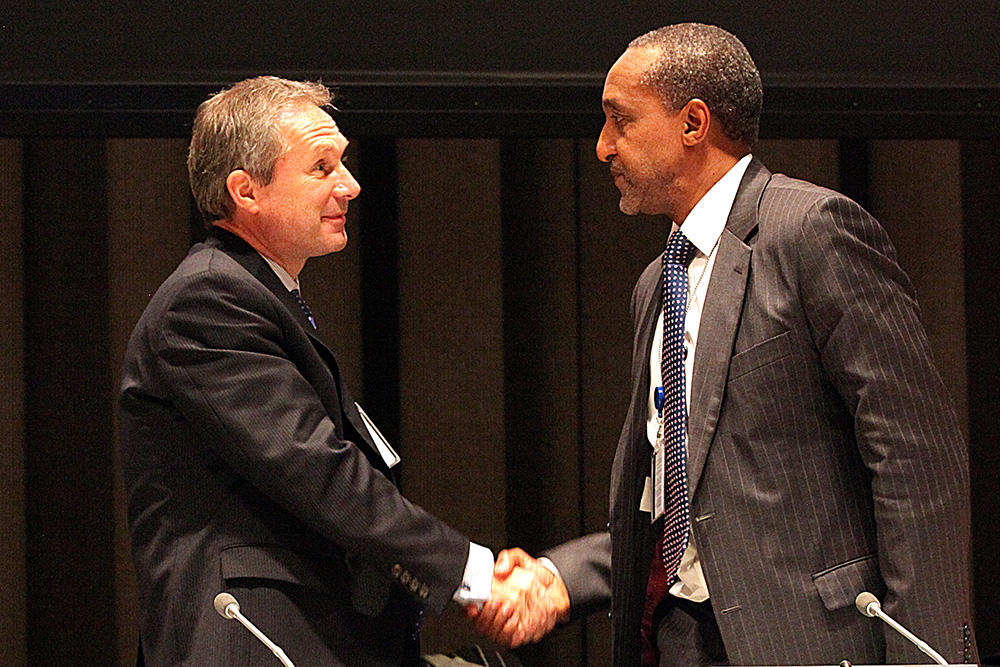 Permanent Representative of Hungary, Csaba Kőrösi, and Permanent Representative of Kenya, Macharia Kamau, Co-Chairs of the Open Working Group, shake hands at the sixth session in December 2013. Photo IISD